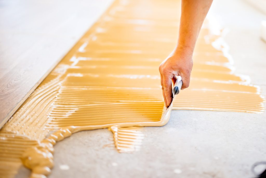 close-up of hand of worker adding glue during parquet installation